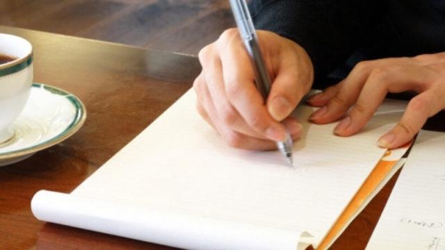 カフェでコーヒー片手にノートにメモをとる男性
